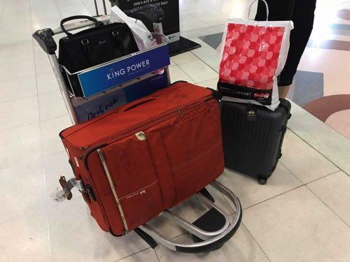 スワンナプーム国際空港にて回転台からスーツケースを受け取る